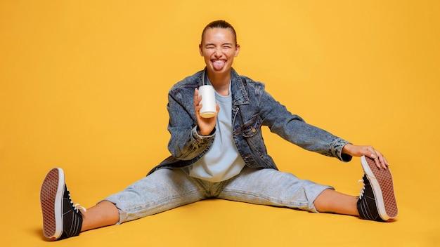 Mulher sorridente com a língua de fora segurando uma lata de refrigerante enquanto está sentada