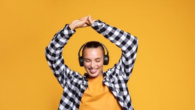 Mulher sorridente com a língua para fora ouvindo música em fones de ouvido