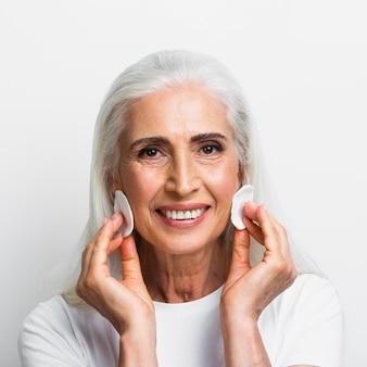 Mulher sorridente com almofadas de algodão no rosto