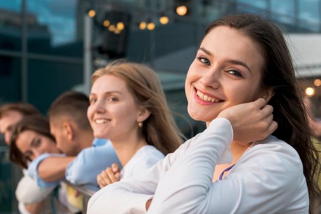 Mulher sorridente, com, amigos, em, fundo