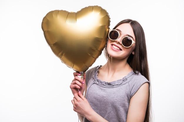 Mulher sorridente com balão em forma de coração.
