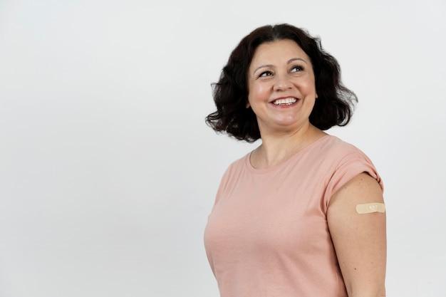 Mulher sorridente com bandagem no braço após a aplicação da vacina