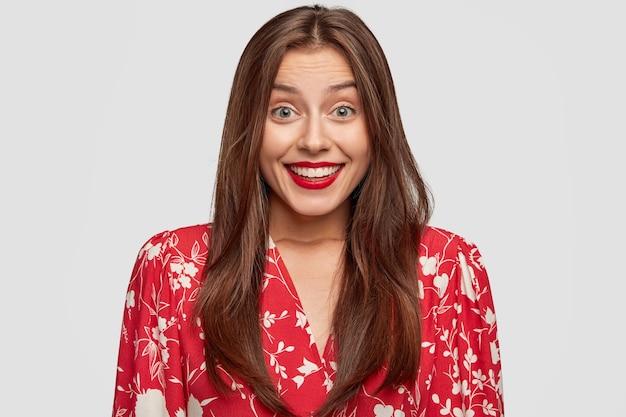 Mulher sorridente com batom vermelho posando contra a parede branca