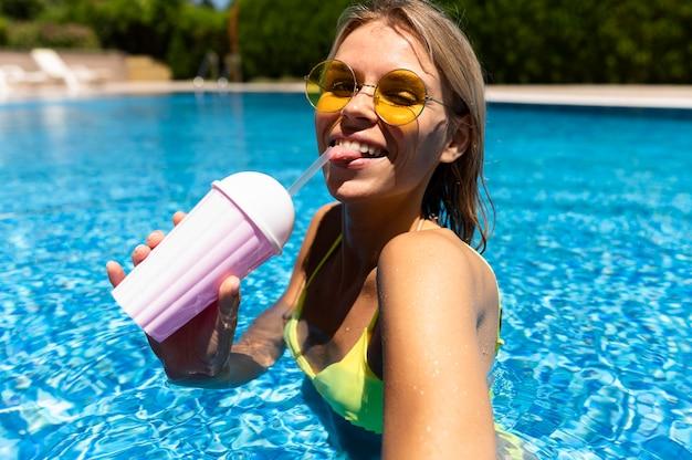 Mulher sorridente com bebida na piscina