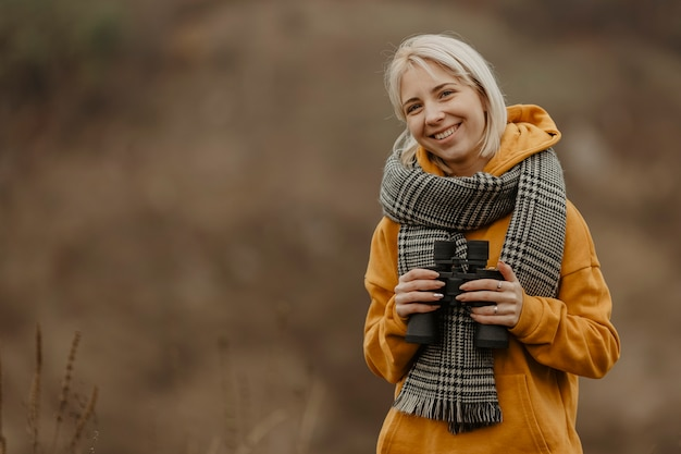 Mulher sorridente com binóculo