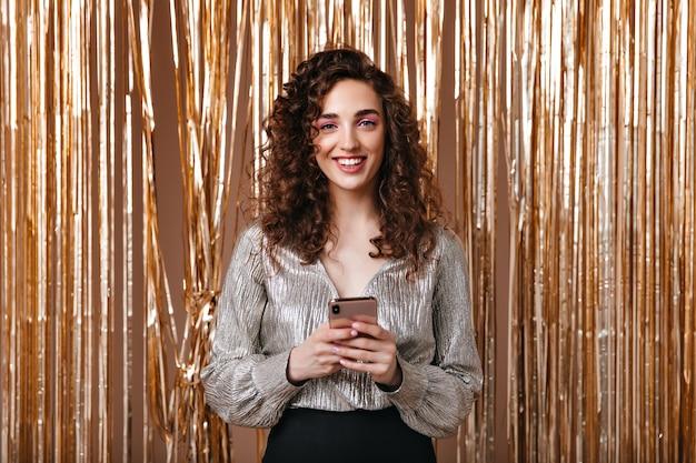Mulher sorridente com blusa prateada segurando o smartphone sobre fundo dourado