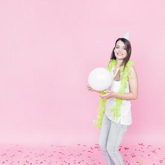 Mulher sorridente, com, boa, ao redor, dela, pescoço, segurando, branca, balloon, contra, rosa, fundo