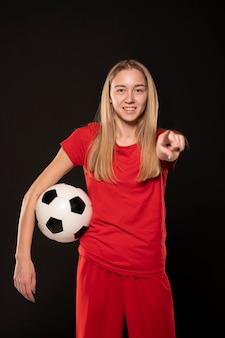 Mulher sorridente com bola de futebol apontando