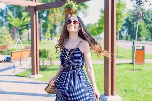 Mulher sorridente com bolsa e óculos de sol