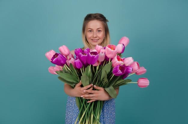 Mulher sorridente com buquê de tulipas cor de rosa e roxas. conceito de verão e primavera.