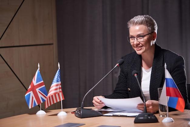 Mulher sorridente com cabelo curto senta-se na conferência de negócios usando o microfone enquanto discursa para os parceiros sentados na mesa. executivos multiétnicos reunidos. retrato de mulher em traje formal