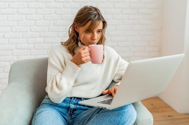 Mulher sorridente com cabelos loiros ondulados, sentada no sofá em casa, trabalhando no laptop e segurando uma xícara de café