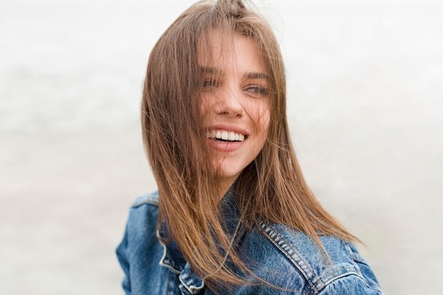 Mulher sorridente com cabelos soprados pelo vento