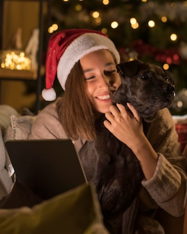 Mulher sorridente com cachorro e chapéu de papai noel segurando um tablet