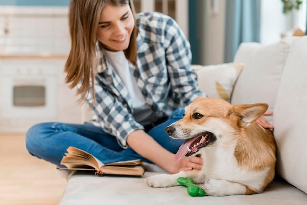 Mulher sorridente com cachorro fofo no sofá