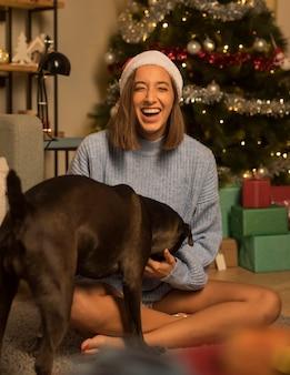 Mulher sorridente com cachorro posando com chapéu de papai noel