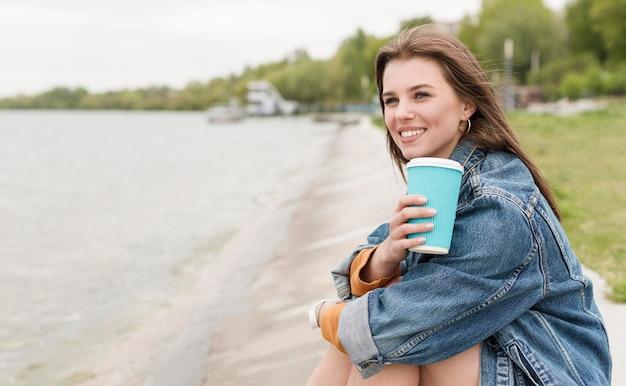 Mulher sorridente com café à beira-mar