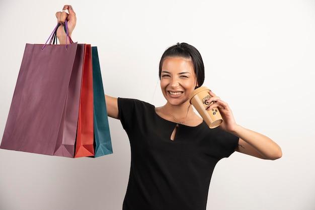 Mulher sorridente com café segurando sacolas de compras.