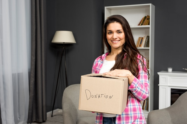Mulher sorridente com caixa dontaion