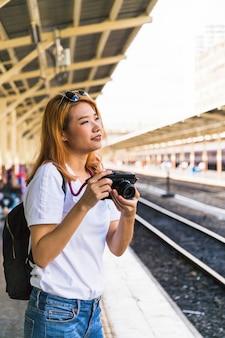 Mulher sorridente, com, câmera, ligado, plataforma