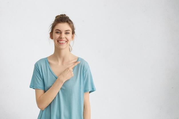 Mulher sorridente com camisa azul apontando para uma parede branca enquanto demonstra algo