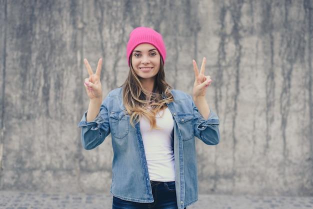 Mulher sorridente com camisa jeans e chapéu rosa mostrando o sinal de vitória na parede cinza