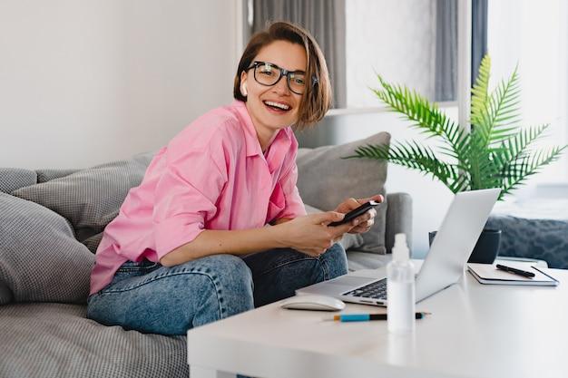 Mulher sorridente com camisa rosa sentada relaxada no sofá em casa à mesa trabalhando online no laptop de casa