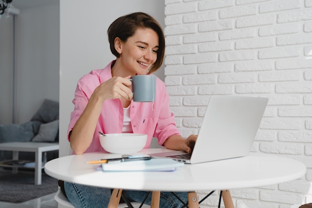 Mulher sorridente com camisa rosa tomando café da manhã em casa na mesa trabalhando online no laptop de casa, comendo cereais