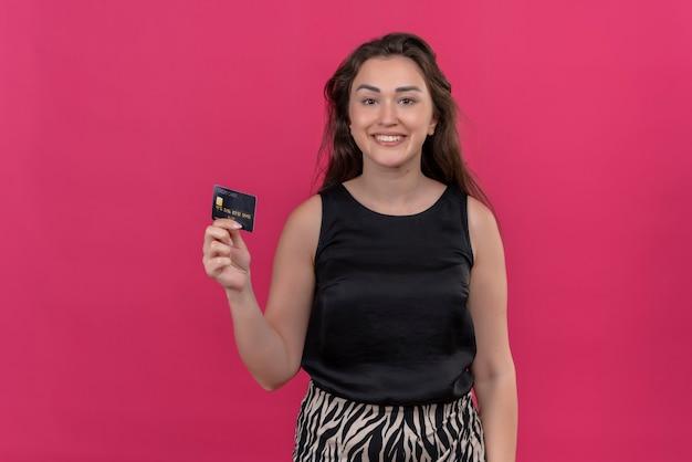 Mulher sorridente com camiseta preta segurando um cartão do banco na parede rosa