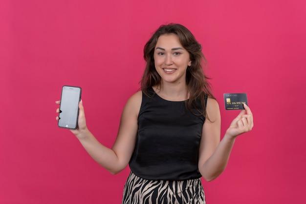 Mulher sorridente com camiseta preta segurando um telefone e um cartão do banco na parede rosa