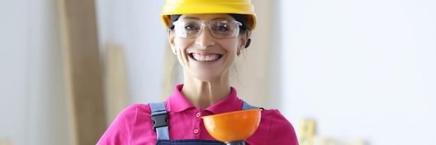Mulher sorridente com capacete amarelo e óculos, segurando o êmbolo na mão. serviços de mulher conceito de encanamento