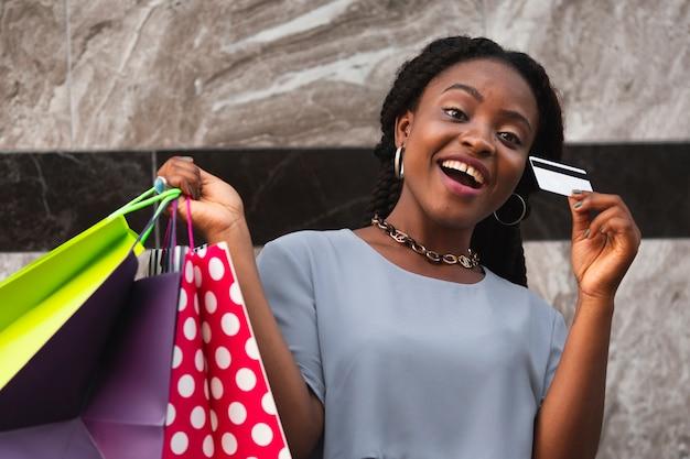 Mulher sorridente com cartão e sacolas de compras