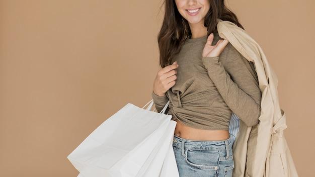 Mulher sorridente com casaco no ombro e sacolas de compras