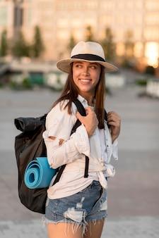 Mulher sorridente com chapéu carregando mochila enquanto viaja sozinha