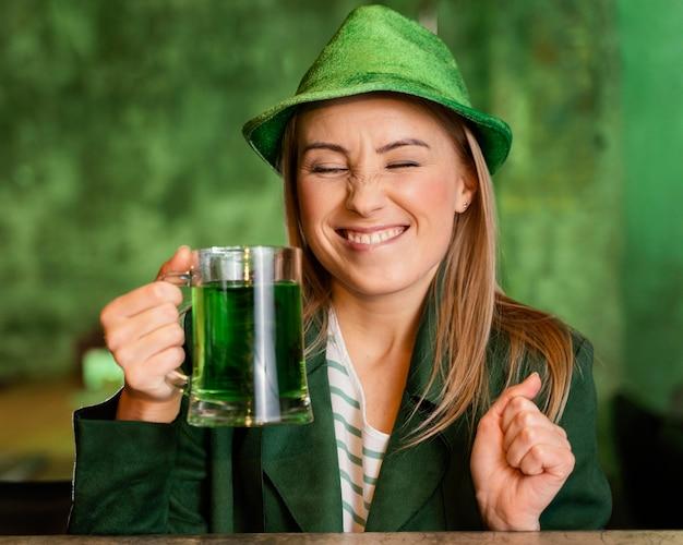 Mulher sorridente com chapéu comemorando st. dia de patrick com bebida