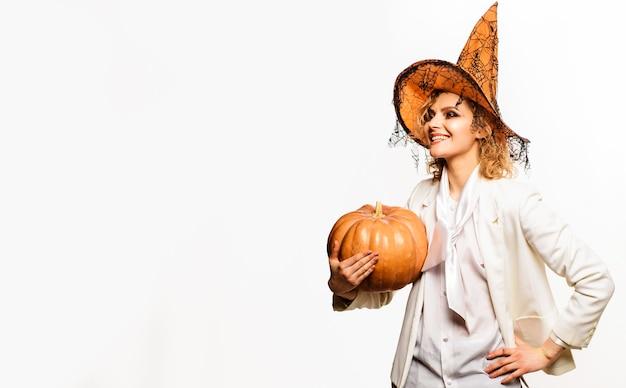 Mulher sorridente com chapéu de bruxa com abóbora de halloween. doçura ou travessura. feliz dia das bruxas. copie o espaço para publicidade.