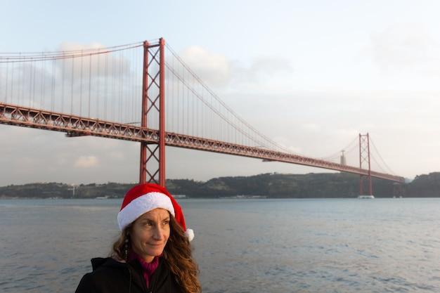 Mulher sorridente com chapéu de natal ao pôr do sol à beira do rio tejo com a ponte 25 de abril em lisboa