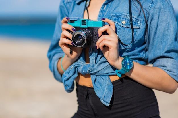 Mulher sorridente com chapéu de palha e roupa elegante de verão, posando com uma câmera retro na praia.