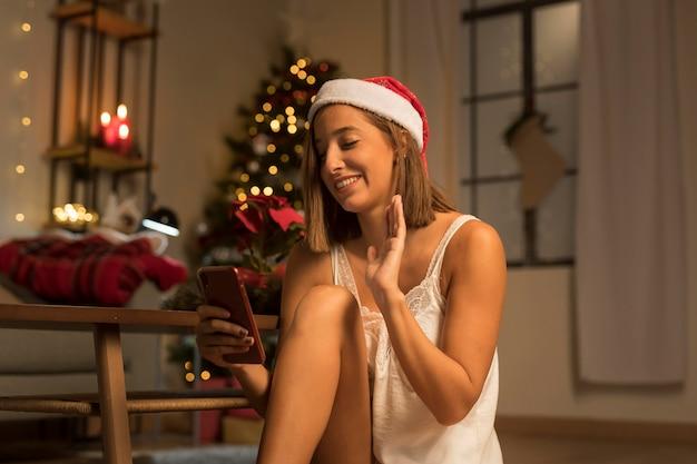 Mulher sorridente com chapéu de papai noel acenando para um smartphone no natal