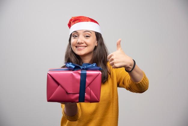 Mulher sorridente com chapéu de papai noel aparecendo um polegar e segurando uma caixa de presente.