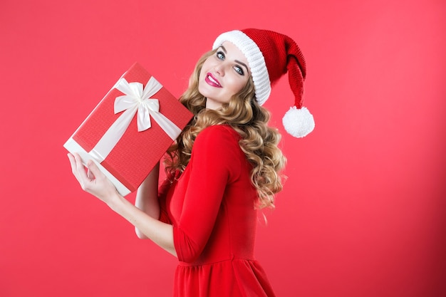 Mulher sorridente com chapéu de papai noel com caixa de presente vermelha. ano novo e natal.