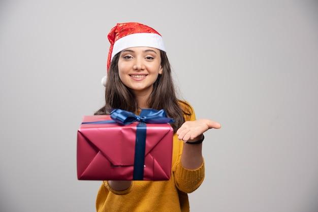 Mulher sorridente com chapéu de papai noel, mostrando uma caixa de presente.