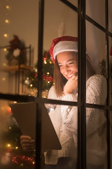 Mulher sorridente com chapéu de papai noel pela janela olhando para um tablet no natal