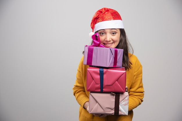 Mulher sorridente com chapéu de papai noel segurando caixas de presente.
