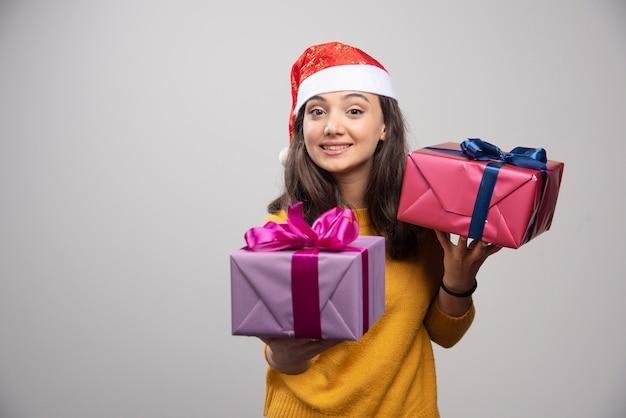Mulher sorridente com chapéu de papai noel segurando nas mãos os presentes de natal.