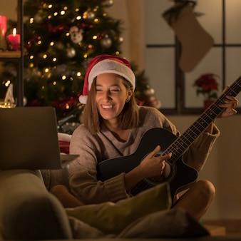 Mulher sorridente com chapéu de papai noel tocando guitarra na frente do laptop