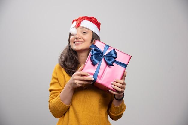 Mulher sorridente com chapéu de papai noel vermelho com presente de natal.