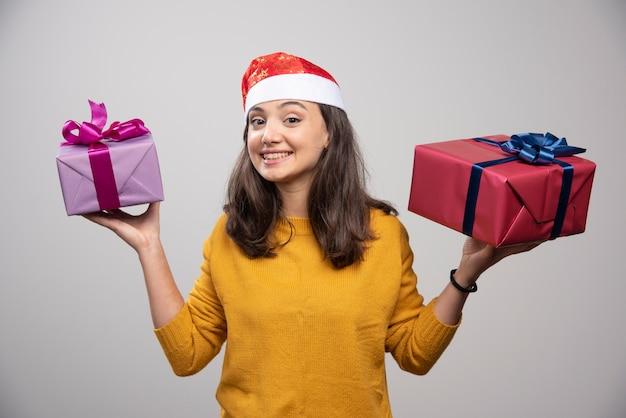 Mulher sorridente com chapéu de papai noel vermelho com presentes de natal.