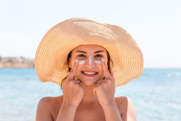 Mulher sorridente com chapéu está aplicando protetor solar no rosto. estilo indiano.