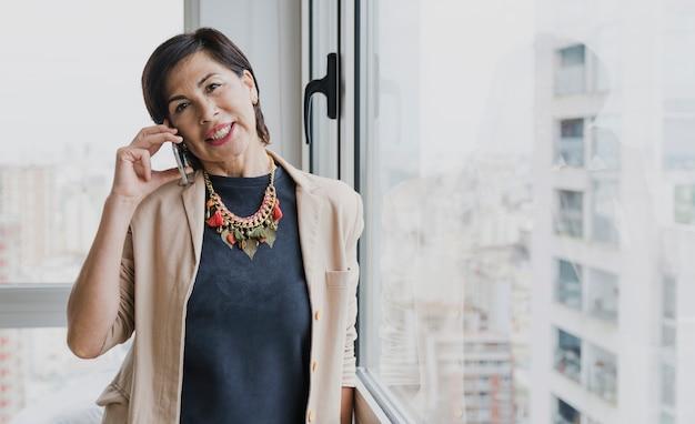 Mulher sorridente com colar falando ao telefone